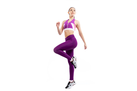 Photo pour A dark-haired woman coach in a sporty pink short top and gym leggings  doing exercise to warm up the legs, alternate knee flexion  on a  white isolated background in studio - image libre de droit