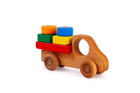 Photo for Photo of a wooden car truck loaded with small colorful wooden geometric figures: a circle, a triangle, a rectangle, a square made of beech on a white isolated background - Royalty Free Image