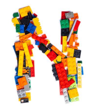 Foto de Letter N of the English alphabet  from multi-colored children's plastic constructor on a white isolated background.  Bright alphabet for kids design - Imagen libre de derechos