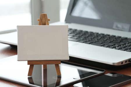 Foto de blank canvas and wooden easel on laptop computer as concept - Imagen libre de derechos