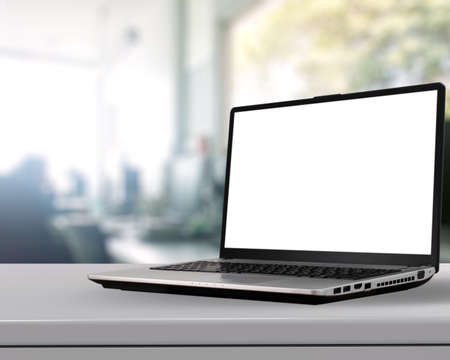 Foto de Laptop with blank screen on white desk with blurred background as concept - Imagen libre de derechos