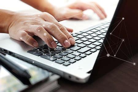 Foto de Close up of business man working on laptop computer with social network diagram on wooden desk as concept - Imagen libre de derechos