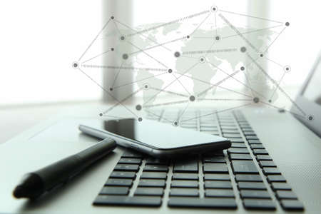 Photo for laptop and mobile phone and stylus with social network diagram on wooden desk as concept - Royalty Free Image