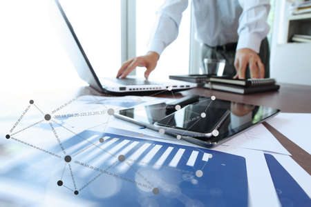 Foto de business documents on office table with digital tablet and man working with smart laptop computer background with social network diagram concept - Imagen libre de derechos