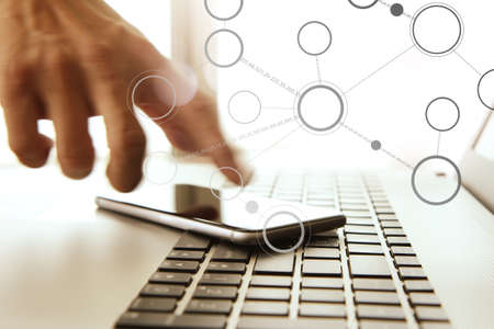Businessman hand using laptop and mobile phone in office