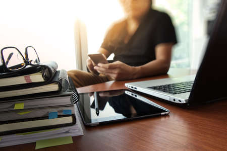 designer hand working with  digital tablet and laptop and notebook stack and eye glass on wooden desk in office