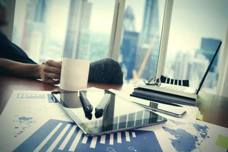 Foto de business documents on office table with smart phone and digital tablet and graph business diagram and man working in the background - Imagen libre de derechos
