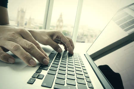 Photo for business man hand working on laptop computer on wooden desk with london city blurred background as concept - Royalty Free Image