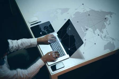 Foto de top view of man working with business documents on office table with digital tablet and man working with smart laptop computer with social media diagram - Imagen libre de derechos