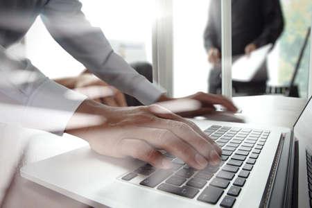 Foto de Close up of business man hand working on laptop computer with business strategy diagram on wooden desk as concept - Imagen libre de derechos