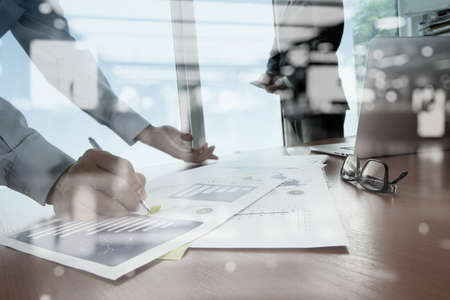 Foto de double exposure of business documents on office table with smart phone and digital tablet and stylus and two colleagues discussing data in the background - Imagen libre de derechos