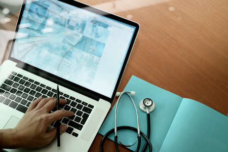Foto de top view of Medicine doctor hand working with modern computer and smart phone on wooden desk as medical concept - Imagen libre de derechos