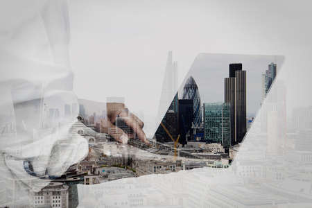 Foto de double exposure of businessman working on his laptop in office with london city background - Imagen libre de derechos