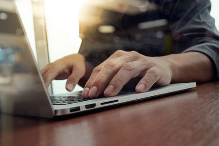 Foto de business man hand working on laptop computer on wooden desk as concept, young man student typing on computer sitting at wooden table - Imagen libre de derechos