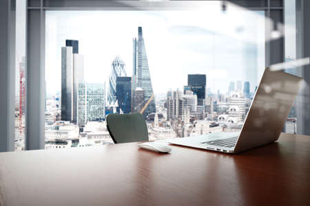 Photo pour Office workplace with laptop and smart phone on wood table with london city background - image libre de droit