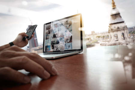 Photo pour designer hand working and smart phone and laptop on wooden desk in office with london city background - image libre de droit
