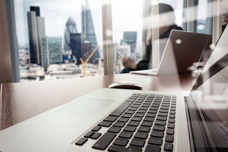 Photo for designer hand working and smart phone and laptop on wooden desk in office with london city background - Royalty Free Image