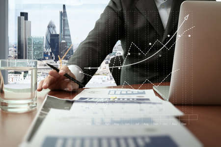 Photo pour business documents on office table with smart phone and digital tablet and graph business diagram and man working in the background with london city view - image libre de droit