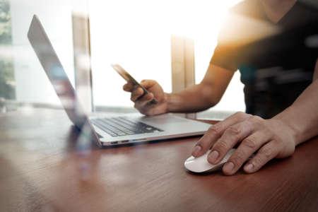 Foto de close up of business man hand working on laptop computer on wooden desk - Imagen libre de derechos