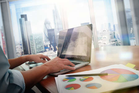 Foto de business documents on office table with smart phone and laptop computer and graph business with social network diagram and man working in the background - Imagen libre de derechos