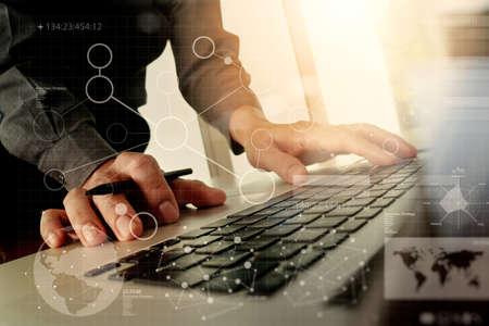 Foto de Close up of business man hand working with digital business layers diagram laptop computer on wooden desk as concept - Imagen libre de derechos