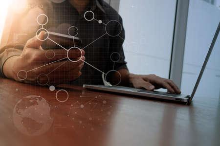 Foto de designer hand working and smart phone and laptop with social media diagram on wooden desk in office - Imagen libre de derechos