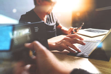 Photo for StartUp Programming Team. Website designer working digital tablet dock keyboard and computer laptop with smart phone and compact server on mable desk,light effect - Royalty Free Image