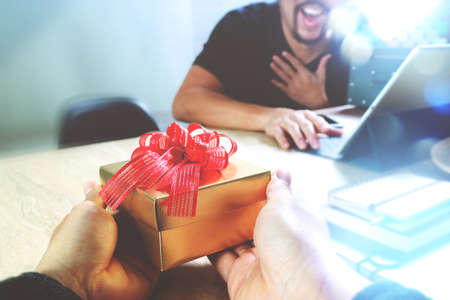 Foto de Gift Giving.business creative designer hand giving his colleague Christmas present in office,filter film effect - Imagen libre de derechos