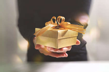 Foto de gift giving,man hand holding a gold gift box in a gesture of giving.blurred background,bokeh effect - Imagen libre de derechos