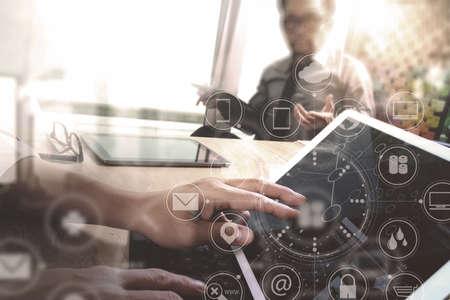 Foto de Co worker Designer hand using mobile payments online shopping,omni channel,in modern office wooden desk,icons graphic interface screen,eyeglass,filter - Imagen libre de derechos