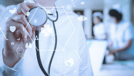 Foto de Healthcare and Medicine concept.smart medical doctor working with stethoscope at modern hospital with VR icon diagram - Imagen libre de derechos