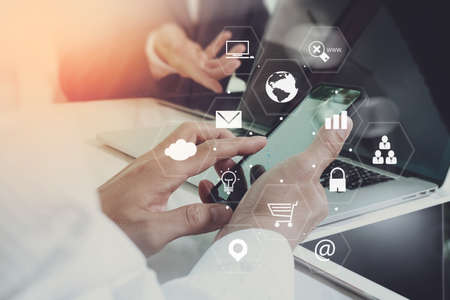 Foto de co working team meeting concept,businessman using smart phone and laptop and digital tablet computer in modern office with virtual interface icons network diagram - Imagen libre de derechos
