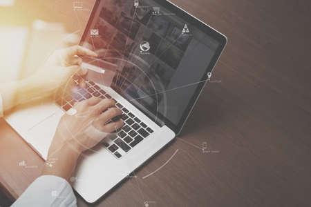 Foto de top view of Hand using credit card and laptop computer on wooden desk with VR icon chart graph diagram - Imagen libre de derechos