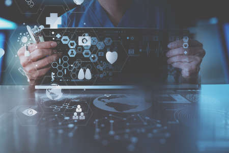 Foto de medical techonlogy concept,smart doctor hand working with modern laptop computer in modern office with virtual icon diagram - Imagen libre de derechos