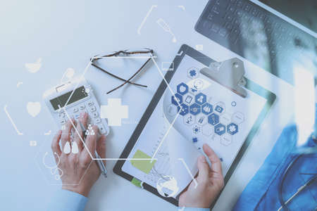 Foto de top view of Healthcare costs and fees concept.Hand of smart doctor used a calculator for medical costs in modern hospital with VR icon diagram - Imagen libre de derechos