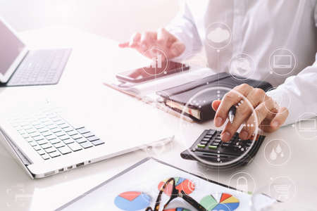 Photo pour businessman hand working with finances about cost and calculator  and latop with mobile phone on withe desk in modern office with VR icon diagram - image libre de droit