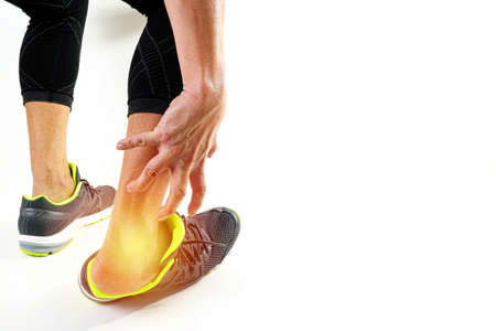 Foto de Runner sportsman holding ankle in pain with Broken twisted joint running sport injury and Athletic man touching foot due to sprain on white background - Imagen libre de derechos