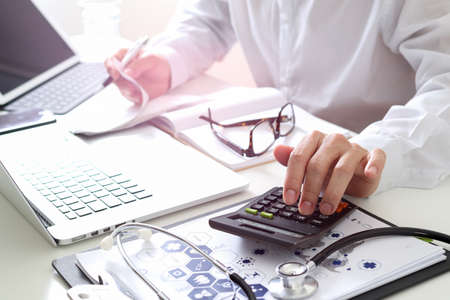 Foto de Healthcare costs and fees concept.Hand of smart doctor used a calculator for medical costs in modern hospital - Imagen libre de derechos