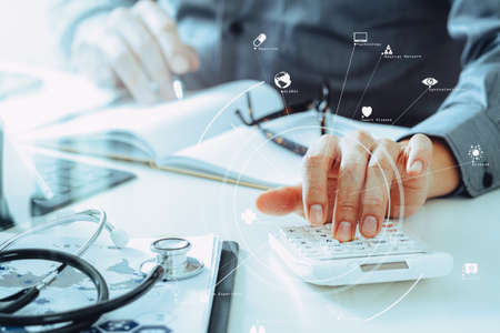 Foto de Healthcare costs and fees concept.Hand of smart doctor used a calculator for medical costs in modern hospital with VR icon diagram - Imagen libre de derechos