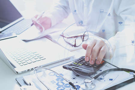 Photo pour Healthcare costs and fees concept.Hand of smart doctor used a calculator for medical costs in modern hospital with VR icon diagram - image libre de droit
