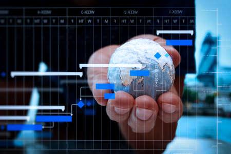 Foto de Project manager working and update tasks with milestones progress planning and Gantt chart scheduling diagram.businessman hand showing texture the world. - Imagen libre de derechos
