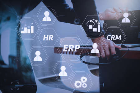 Foto de Architecture of ERP (Enterprise Resource Planning) system with connections between business intelligence (BI), production, CRM modules and HR diagram.Man using VOIP headset with digital tablet computer. - Imagen libre de derechos