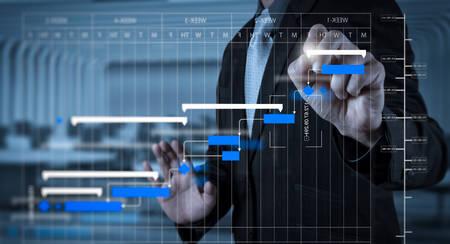 Foto de Project manager working and update tasks with milestones progress planning and Gantt chart scheduling diagram - Imagen libre de derechos