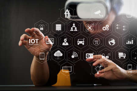Photo pour Internet of Things (IOT) technology with AR (Augmented Reality) on VR dashboard. businessman wearing virtual reality goggles in modern office with Smartphone using with VR headset with screen icon diagram - image libre de droit