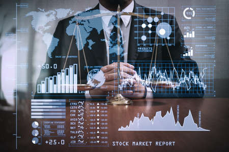 Photo pour Investor analyzing stock market report and financial dashboard with business intelligence (BI), with key performance indicators (KPI).justice and law concept.Male lawyer in the office with brass scale on wooden table. - image libre de droit