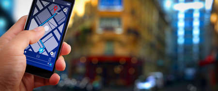 Foto de Close up of Tourist using GPS map navigation on smartphone application screen for direction to destination address in the city with travel and technology concept. - Imagen libre de derechos