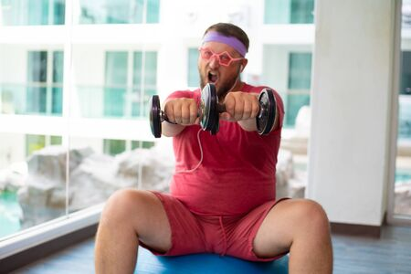 Foto per Funny fat male in pink glasses and in a pink t-shirt is engaged with dumbbells on a fit ball in the gym depicting a girl. - Immagine Royalty Free