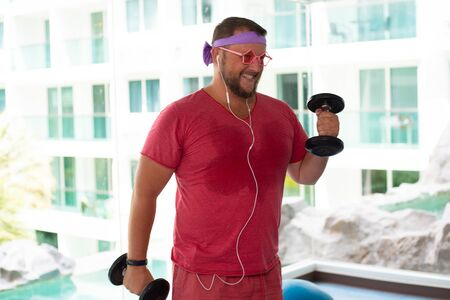 Foto per Funny fat male in pink glasses and in a pink T-shirt engaged with dumbbells in the gym portraying a girl. - Immagine Royalty Free