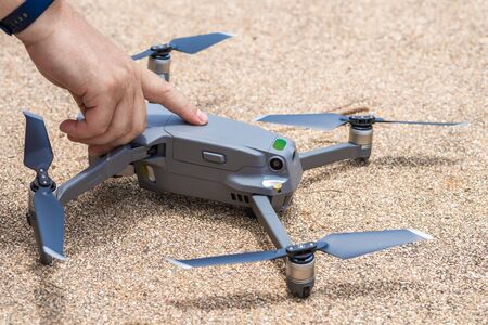 Foto de Male finger presses the launch button of the drone for flight, with which you can take photos and video filming, close-up. - Imagen libre de derechos