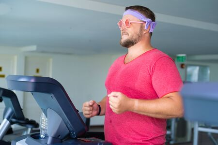 Foto per Funny fat male in pink glasses and in a pink t-shirt is engaged on a treadmill in the gym depicting a girl. - Immagine Royalty Free